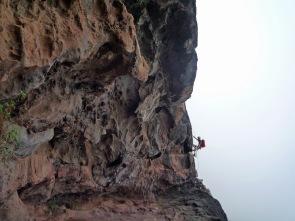 Climbing the corner of a cave on the Via Ferrata La Guagua on Gran Canaria.