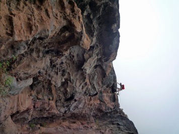 Climbing the corner of a cave on the Via Ferrata La Guagua on Gran Canaria.