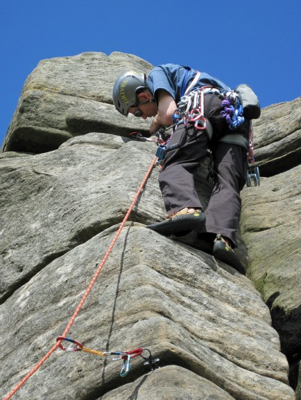 Placing gear on Pillar Arete (VD*) on a hot June day at Stanage Edge.