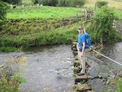 Crossing the River Dove on a walk in the Yorkshire Dales in August.