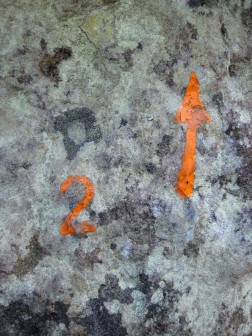 The painted mark and arrow showing the start and direction of orange problem number 2 at Rocher des Potets.