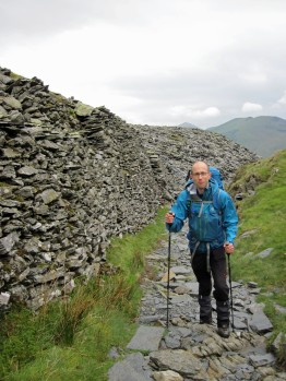 Me walking past a wall of stacked slates in a disused quarry below Yr Aran.