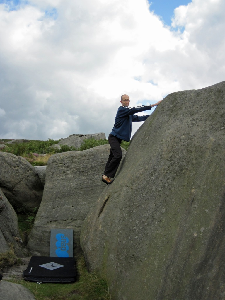 Me climbing Wall Past Slot on The Pock Block boulder at Burbage South Valley.
