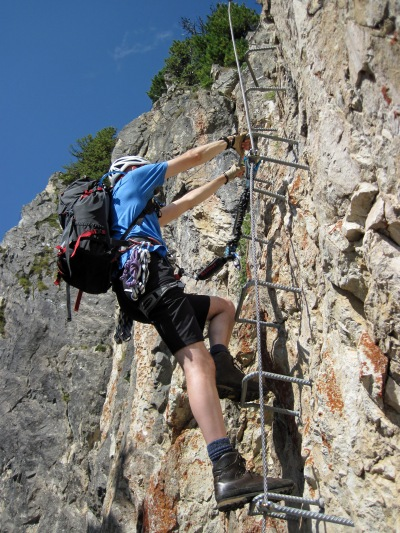 Me climbing a ladder of stemples on the Klettersteig Knorren.
