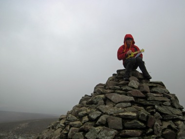Marcus playing his ukulele on top of Dunkery Beacon.
