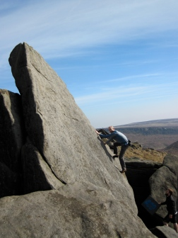 Climbing the boulder problem Big Slab Right (V0+, 5a) on a wonderfully sunny day at Higgar Tor.