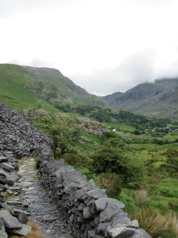Walking along the edge of the Dinorwig Slate Quarry, with Nant Peris and the Llanberis Pass in the distance.