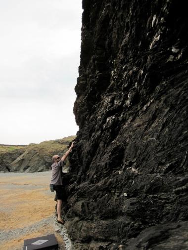 Bouldering on the black rock of Lon Isallt Bay