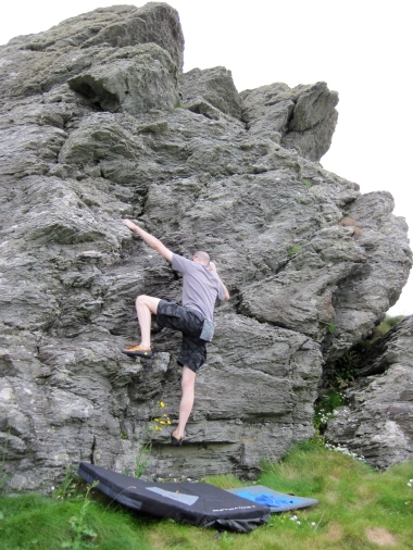 Bouldering on the little crag above Lon Isallt Bay.