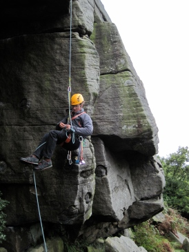 Sam abseiling (rappelling) past a knot.