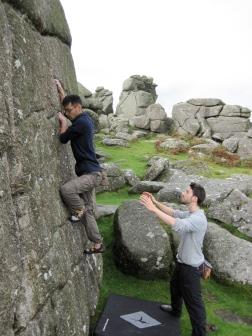 Leo climbing on the Warm-Up boulder at Bonehill with Josh spotting him.