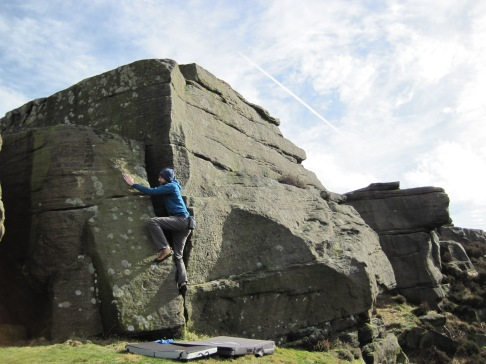 Me climbing Bones (V0 4c) at the Cioch Top Boulders at Curbar Edge.