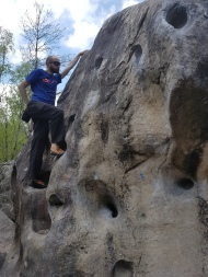 Me getting some chalk while climbing the pocket-filled orange 13 problem at Roche aux Sabots.
