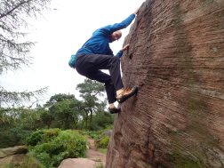 Climbing Joe's Portholes (V0+ 5a) on Joe's Boulder at the Roaches.