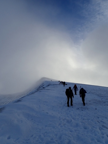 Heading up a snowy and icy ridge to the summit of Corn Du.
