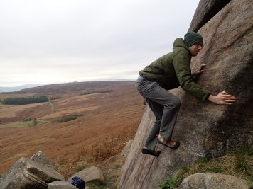 Me climbing the problem Wall End Slab Direct Start (V0 4c) at Stanage Plantation.