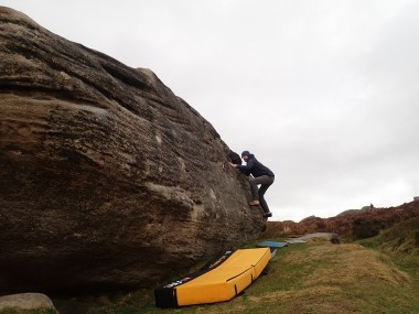 Climbing the very fun traversing problem Walking the Dog, on The Dog boulder at Burbage South Valley.